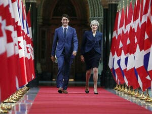 Canadian Prime Minister Justin Trudeau and British Prime Minister Theresa May walk down the Hall of Honour in Ottawa, Ontario (AFP/File Photo)