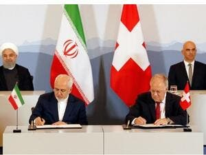Iranian President Hassan Rouhani (top- L) and Swiss President Alain Berset (top-R) watch as Iranian Foreign Minister Mohammad Javad Zarif (L) and Swiss Economic Minister Johann Schneider-Ammann sign an agreement in Bern on July 3, 2018. (AFP)
