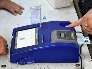 An Iraqi voter has her biometric voting card checked with her fingerprint upon arriving at a poll station for the parliamentary elections in the northern multi-ethnic city of Kirkuk on May 12, 2018. (Marwan Ibrahim/ AFP)