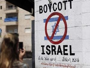 A tourist photographs a sign painted on a wall in the occupied West Bank town of Bethlehem on June 5, 2015, calling to boycott Israeli products. (AFP)