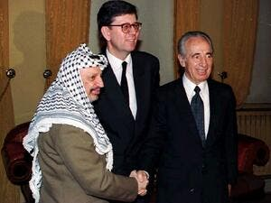 This file photo taken on January 22, 1994 shows Israeli Foreign Minister Shimon Peres (R) and PLO Chairman Yasser Arafat (L) shaking hands as they pose with the new Norwegian Foreign Minister Bjoern Tore Godal in Oslo. (AFP/Stringer)