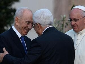 Israeli President Shimon Peres (left) shakes hands with Palestinian leader Mahmud Abbas as Pope Francis looks on following a peace summit at the Vatican, on June 8, 2014 (AFP/Filippo Monteforte)