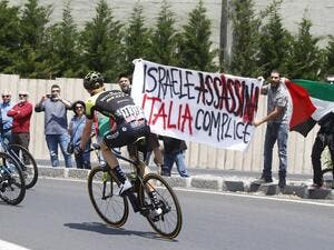 "Australia's rider of team Mitchelton-Scott Jack Haig rides past protesters holding a banner reading ""Israel assassinate, Italy complicit"" before the start of 4th stage between Catania and Caltagirone (Sicily) of the 101st Giro d'Italia, Tour of Italy cycling race, on May 8, 2018 in Catania. (Luk Benies, AFP/File Photo"
