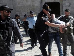 Israeli forces arrest a Palestinian man after Friday prayers at the entrance of Damascus Gate outside the Old City of al-Quds. (AFP/ File)