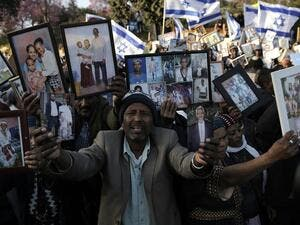 Ethiopian Israelis hold pictures of relatives as they protest in front of the Knesset in Jerusalem. (AFP/ File Photo)