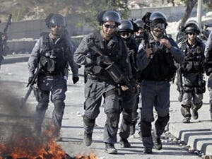 Israeli security officers run past burning tires during clashes with Palestinian protesters in the Issawiya district of Arab east Jerusalem on October 24, 2014. (AFP/ Ahmad Gharabli)