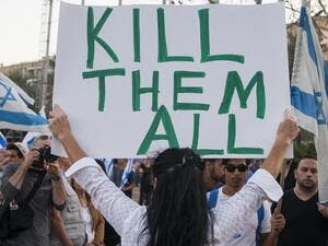An Israeli woman holds up a sign with 'Too many terrorists in prison' on one side and 'Kill them all!' on the other - in reference to Palestinians. (AFP/File)