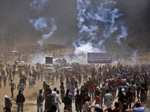 Palestinians run for cover from tear gas during clashes with Israeli security forces near the border between Israel and the Gaza Strip, east of Jabalia/AFP
