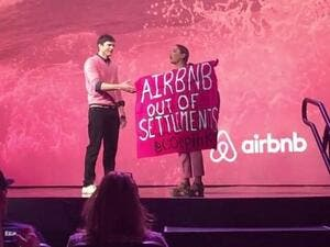 A protester against Airbnb's listing of West Bank settlement rentals during an interview with Ashton Kutcher at Airbnb Open in Los Angeles in 2016. (Screenshot/YouTube)