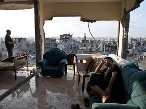 Two young men sit among the aftermath of brutal Israeli offensive on Gaza. (AFP/Roberto Schmidt)