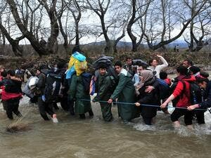 Refugees formed a human chain across the river to help people cross into Macedonia. (AFP/File)