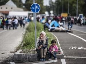 A mother and child sit on the street contemplatively. (AFP/Armend Nimani)