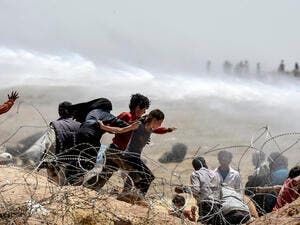 Turkish soldiers use water cannon to move Syrian refugees from border fences at Akcakale in Sanliurfa province, on June 13, 2015. (AFP/Bulent Kilic)