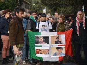 Protesters hold an Italian flag covered with photos of murdered Italian student Giulio Regeni. (AFP/File)