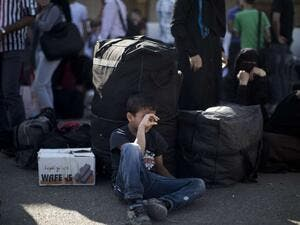 A Palestinian boy waits with his family to cross into Egypt at the Rafah crossing between Egypt and the southern Gaza Strip. (AFP/Mahmud Hams)