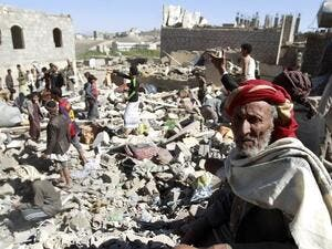 A Yemeni man sits on the rubble as people search for suvivors in houses destroyed by airstrikes. (AFP/File)