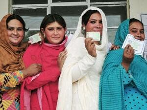 Pakistani voters pose with their national identity cards as they queue to cast their ballots at a polling station during the general election in Rawalpindi. (AFP/ File)