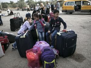 Palestinian children wait as they wait to cross with their families into Egypt through the Rafah border crossing on October 16, 2016 in the southern Gaza Strip. (AFP/Said Khatib)