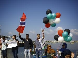 Palestinians show their solidarity with a Gaza-bound flotilla of international activists attempting to break the Israeli blockade on the Hamas-run Gaza Strip, on October 5, 2016 at the port in Gaza City. (AFP/Mohammed Abed)