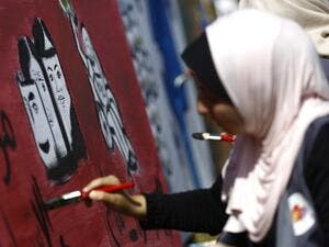 A Palestinian art student paints as she takes part in a festival marking the World Mental Health Day on October 11, 2016 in Gaza City. (AFP/Mohammed Abed)