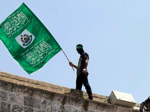 In a file photo, a demonstrator carries a Hamas flag on the roof of occupied Jerusalem's Al-Aqsa mosque, June 3 2015. (AFP/Ahmad Gharabli)