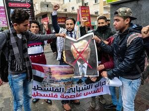 Palestinian protesters prepare to burn a picture of US President Donald Trump in the southern Gaza Strip town of Rafah on December 6, 2017. (Said Khatib/AFP)