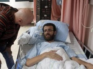 Mohammed al-Qiq, a Palestinian prisoner who carried out hunger strike, talks to a man in a hospital in the northern Israeli town of Afula on February 5, 2016. (AFP/Ahmad Gharabli)