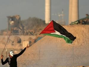 A masked Palestinian protester carries a national flag as he hurls stones during a demonstration calling for an end to the Israeli blockade on Gaza. (MAHMUD HAMS / AFP)