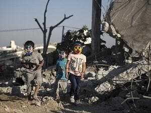 Palestinian children play in the rubble of buildings, reportedly destroyed during the 50-day war between Israel and Hamas militants. (AFP / MOHAMMED ABED)