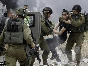 Israeli soldiers detain a Palestinian protester in the West Bank town of Tulkarem. (Jaafar Ashtiyeh/ AFP)