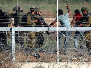 Israeli soldiers arrest Palestinians who tried to approach the Gaza fence during clashes east of Gaza City on May 15, 2018. (AFP/ File Photo)