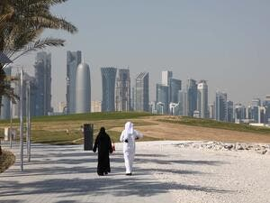 Arabic couple walking in front of the Doha downtown skyline. (Shutterstock/Philip Lange)