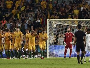 Australian players (L) celebrate their third goal as Jordan goalkeeper Amer Shafi (C) looks on during the World Cup Asian qualifier football match between Australia and Jordan in Sydney on March 29, 2016.