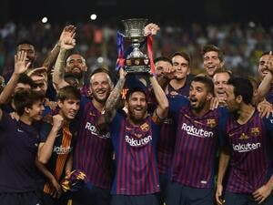 Barcelona's Argentinian forward Lionel Messi (C) carries the cup as they celebrate at the end of the Spanish Super Cup final between Sevilla FC and FC Barcelona at Ibn Batouta Stadium in the Moroccan city of Tangiers on August 12, 2018.