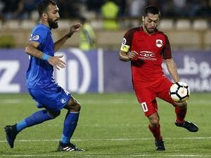 Esteghlal's midfielder Roozbeh Cheshmi (L) vies for the ball with Al-Rayyan's midfielder and captain Rodrigo Tabata during the AFC Champions League football match between Iran's Esteghlal and Qatar's al-Rayyan at the Azadi stadium in Tehran, on April 2, 2018.