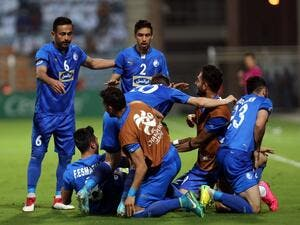 Iranian club Esteghlal's players celebrate after scoring a goal against Saudi club Al-Hilal during their Asian Champions League football match on February 20, 2018 at al-Seeb stadium in Muscat.