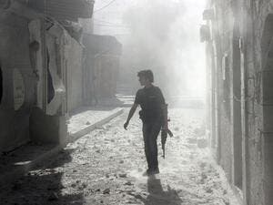 A soldier stands among debris inside Syria (AFP/FILE)