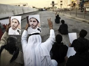 Bahraini demonstrators hold up photos of detained Shiite cleric and opposition leader Sheikh Ali Salman in a suburb of the capital Manama.  (AFP/Mohammed al-Shaikh)