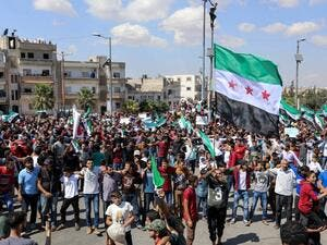 Syrians from Idlib and its surrounding towns wave the flag of the opposition and chant slogans as they gather for an anti-government demonstration in a main square on September 14, 2018. (OMAR HAJ KADOUR / AFP)