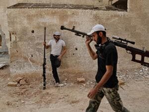 Syrian rebel fighters from the Faylaq al-Rahman brigade carry their homemade 12.7mm sniper rifle in Ain Tarma, in the eastern Ghouta area, a rebel stronghold east of the capital Damascus, on July 20, 2017 (Abdulmonam Eassa/AFP