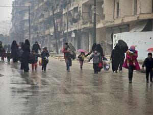 Under the hail of bullets, women and children hurry to leave one of the areas in south Damascus fought over by regimes forces and opposition groups, (AFP/ File Photo)