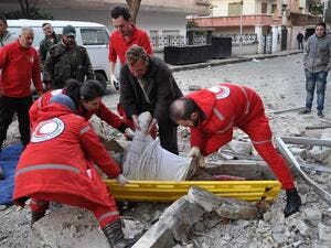 Syrian Red Crescent personnel evacuate the body of a man following a reported mortar strike by rebel fighters in a government-held part of the Syrian city of Homs, on February 10, 2017. (AFP/Stringer)