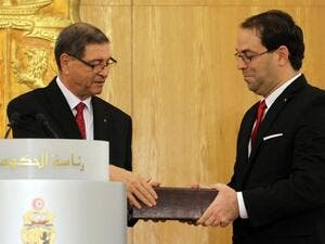 Tunisia's new Prime Minister Youssef Chahed and outgoing PM Habib Essid exchange documents during the handing-over ceremony in Carthage on August 29, 2016. (AFP/Stringer)