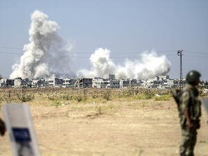 Turkish border guards watch as smoke rises from an airstrike in Syria. (AFP/File)