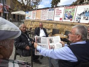 People sit next to campaign posters for parliamentary elections at a cafe in the northern part of Nicosia in the Turkish Republic of Northern Cyprus on January 3, 2018. (AFP/ File)