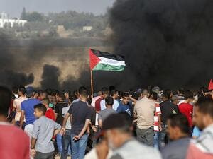 Palestinian protesters wave their national flag as they gather during a demonstration at the Israel-Gaza border, east of Khan Yunis in the southern Gaza Strip on August 10, 2018. (Said KHATIB / AFP)