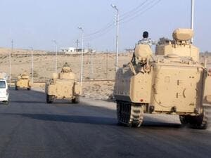 A convoy of Egyptian armoured vehicles heads along a road in El-Arish. (AFP/File)