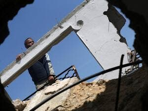 A Palestinian worker checks a house that was destroyed during the 50-day war between Israel and Hamas-led militants in the summer of 2014, east of Gaza City on March 23, 2016. (AFP/Mohammed Abed)