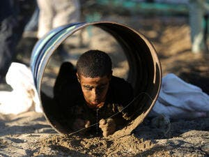 A Palestinian youth crawls through a tunnel during a summer physical training camp run by Hamas in Gaza City on June 21, 2013. (Source: AFP/MOHAMMED ABED)