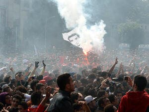 Egyptian fans of Al-Ahly football club wave a flag bearing the portrait of a victim of a football riot as they celebrate outside the club's headquarters in Cairo on Saturday. (AFP)